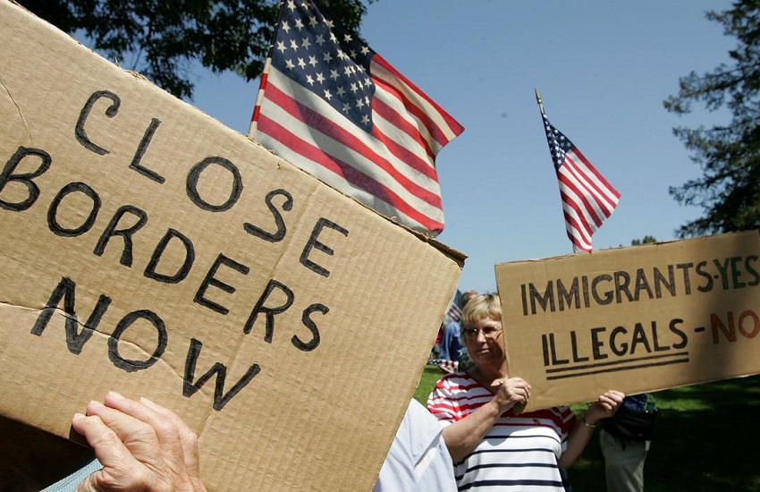 Picture of people holding signs saying close borders now