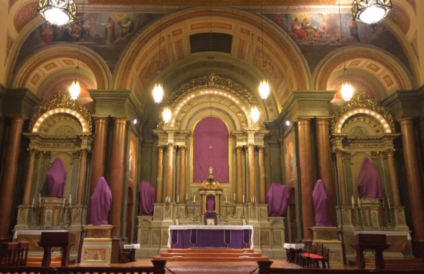 The statues in a Church are veiled in purple cloths during Passiontide
