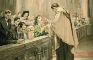 Priest giving Holy Communion to the faithful