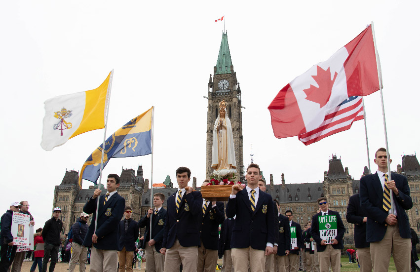 School boys marching at the March for Life with the Pilgrim statue of Our Lady